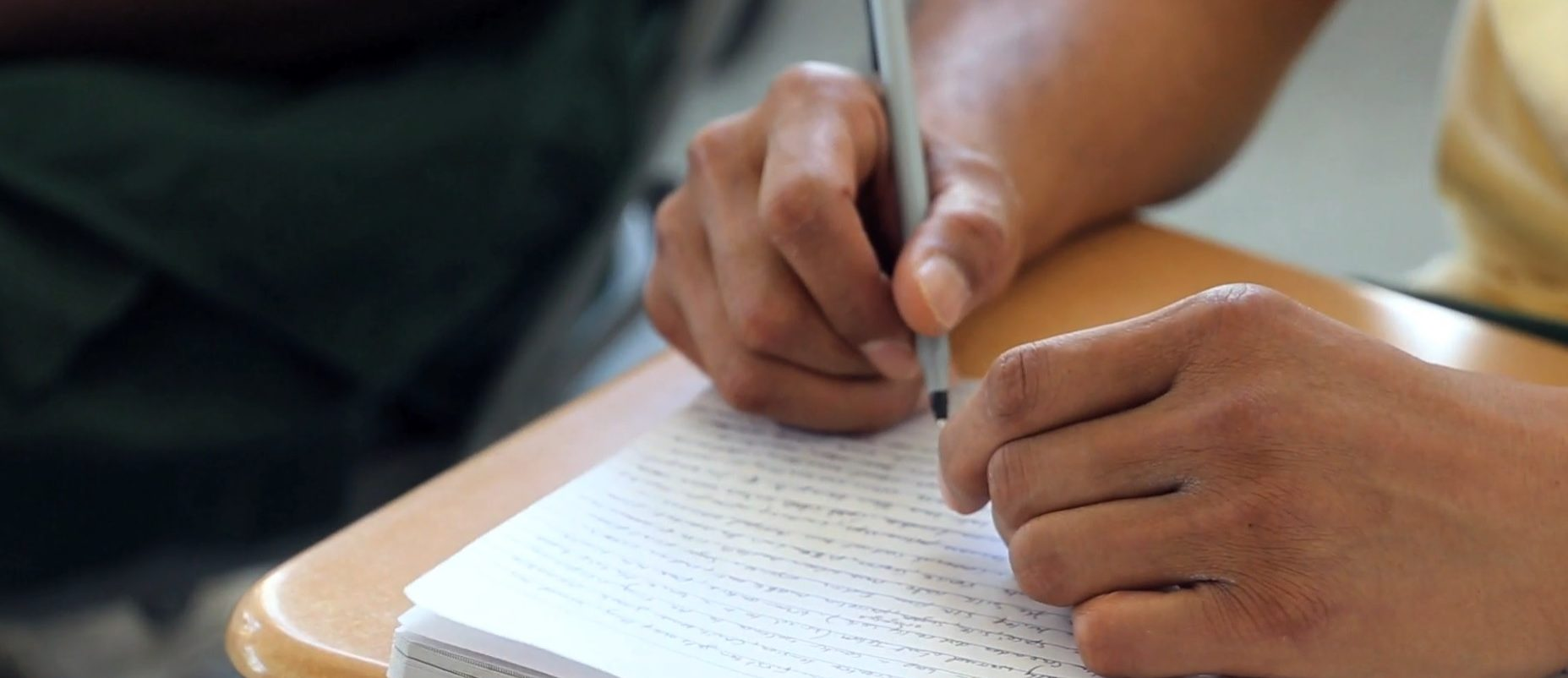 Student writing in a book