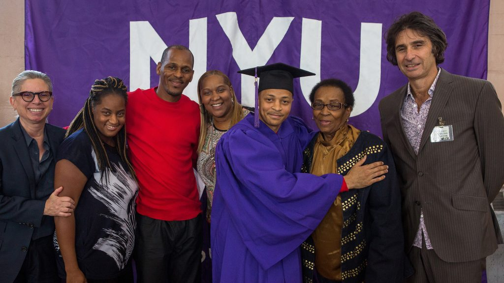 Graduate with his family in front of NYU banner