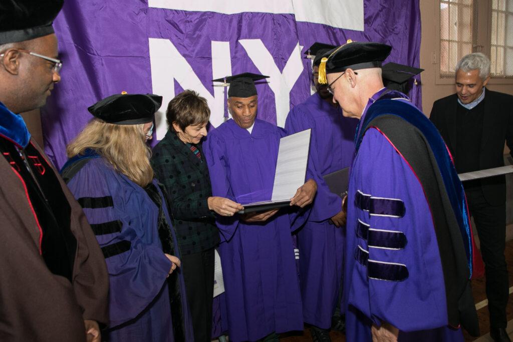 Student holding diploma at 2019 graduation at prison